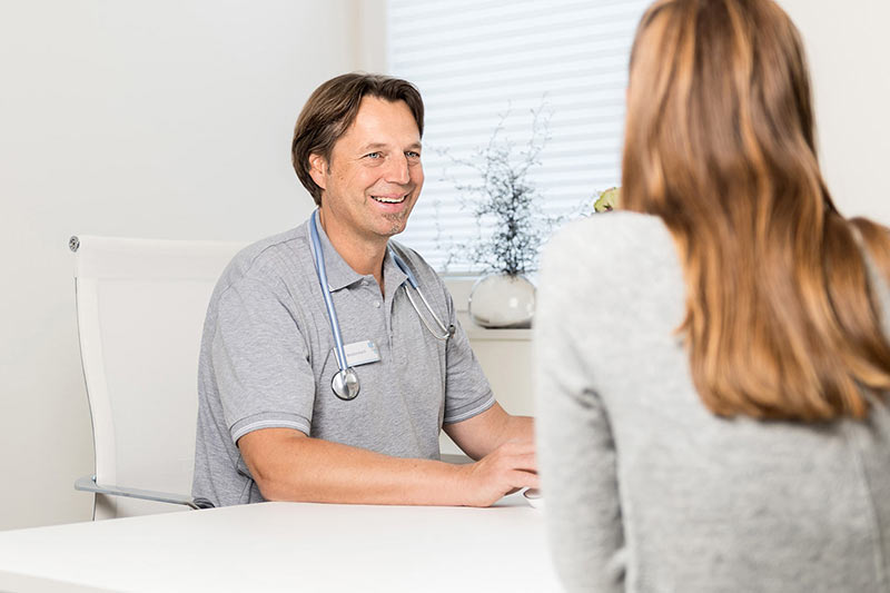 Auf diesem Foto sieht man den Arzt Frank Breitenbach im Gespräch mit einer Patientin.