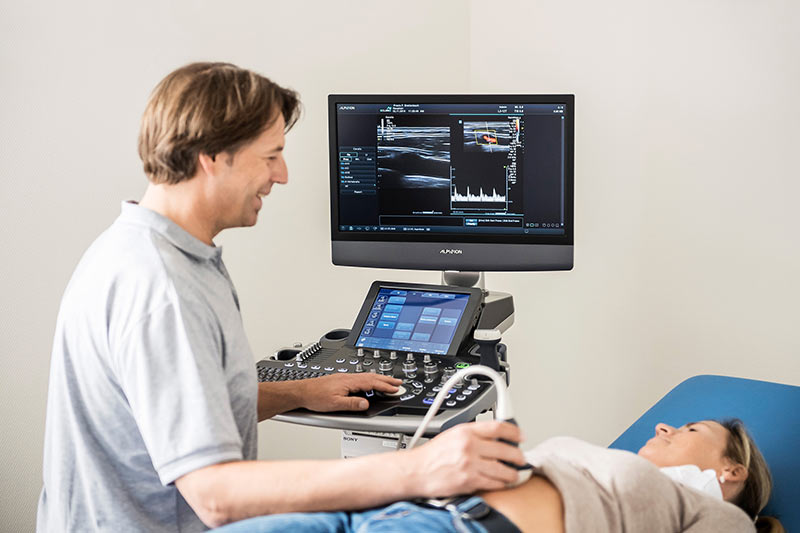 Auf diesem Foto untersucht Allgemeinmediziner Frank Breitenbach den Bauchraum einer Patientin mit dem Sono.