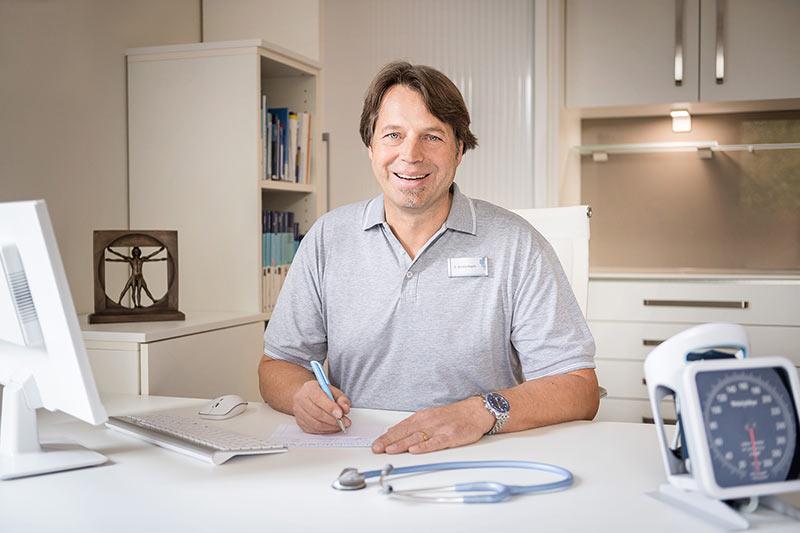 Hier auf dem Foto sieht man den Arzt Frank Breitenbach am Schreibtisch.